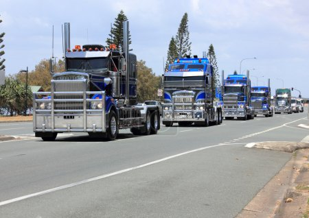 Convoy of blue trucks on highway