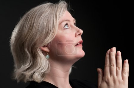 A Caucasian woman praying in the darkness....