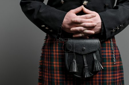 Photo for A man's hand clasped over a Scottish kilt and purse. - Royalty Free Image