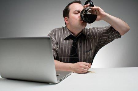 Man Drinking Coffee To Stay Awake At Work