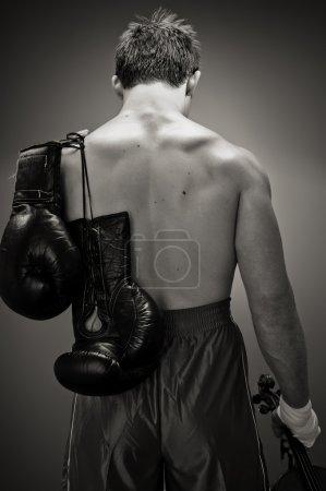 Photo pour Un boxeur maussade est suspendu à sa tête et est titulaire d'un violon dans sa main droite qui est sa véritable passion mais ne sera jamais en mesure de jouer à nouveau. - image libre de droit