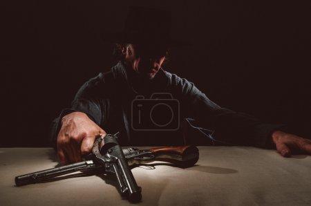 Wild west Gunslinger with guns sitting by the tabl...