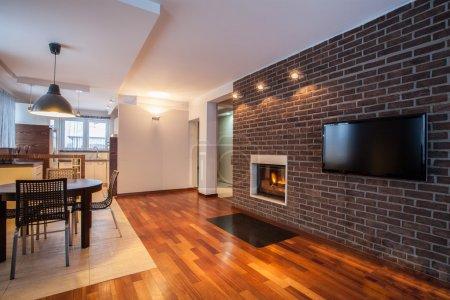 Photo pour Maison de campagne - salle à manger avec mur de briques et cheminée - image libre de droit