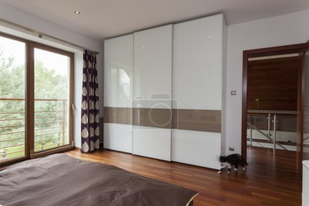 Photo for Contemporary bedroom with balcony and huge wardrobe - Royalty Free Image