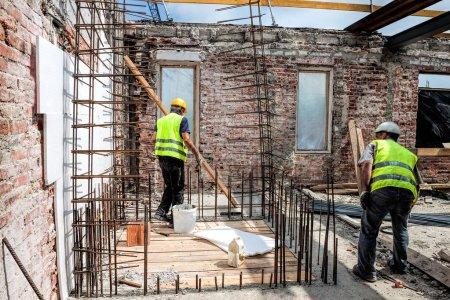 Photo pour Constructeurs à l'œuvre à l'intérieur de la structure du bâtiment - image libre de droit