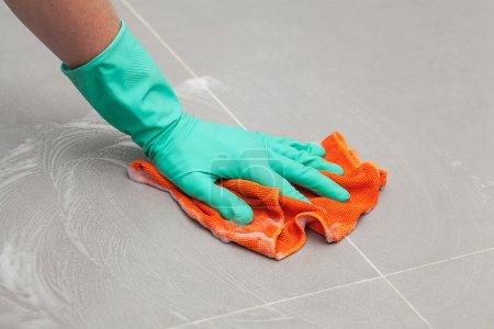Photo pour Un homme dans un gant nettoie le sol avec un chiffon humide - image libre de droit