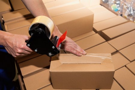 Photo for Worker using adhesive tape to close the boxes - Royalty Free Image