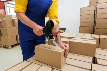 Photo for Factory worker with packing tape gun dispenser finishing a delivery - Royalty Free Image