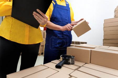 Photo for Manager showing customer order to factory worker - Royalty Free Image