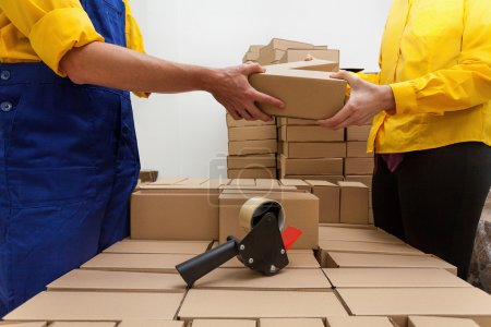 Photo for Factory workers packaging a products into a boxes - Royalty Free Image