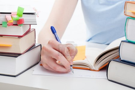 Photo for Student reading a book and writing the notes - Royalty Free Image