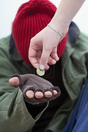 Photo for Women giving a coin for homeless poor man - Royalty Free Image