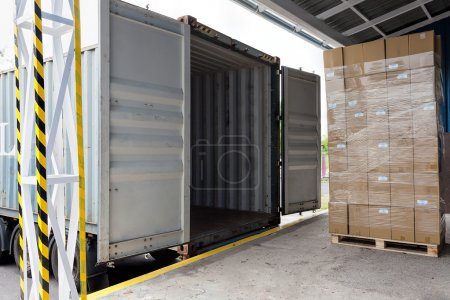 Photo for Forklift with carton boxes loading the truck - Royalty Free Image
