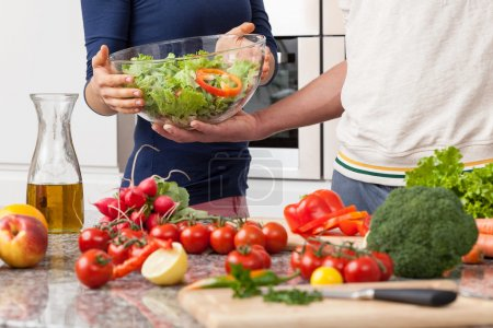 Foto de Novio ayudando a su novia en la fabricación de una ensalada para la cena - Imagen libre de derechos