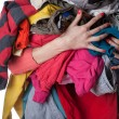 Woman holding a huge pile of clothes...