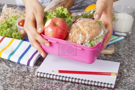 Photo for Mother giving healthy lunch for school in the morning - Royalty Free Image