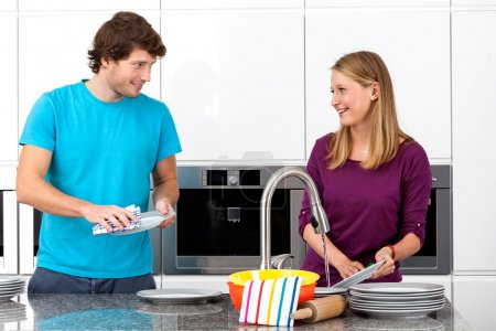 Photo for Young couple cleaning together after dinner - Royalty Free Image