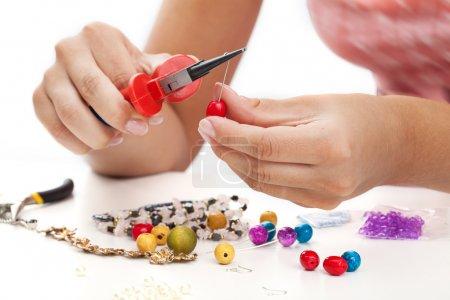 Photo pour Une personne concevant les colorés boucles d'oreille avec perles de plactic - image libre de droit
