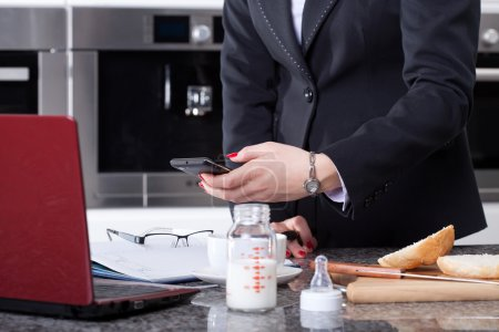 Modern woman preparing meal for child and working at morning