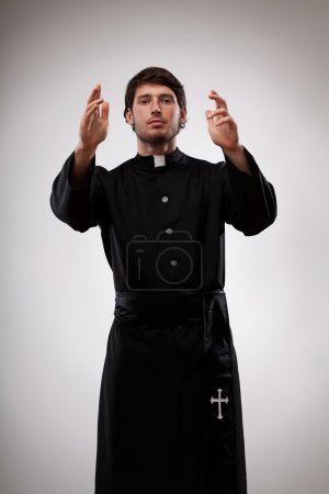 Young priest is gesturing to believers