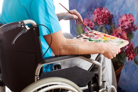 Photo for Disabled person in a wheelchair painting a picture - Royalty Free Image