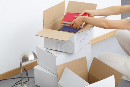 Photo for Plenty of cardboard boxes being filld by a man - Royalty Free Image