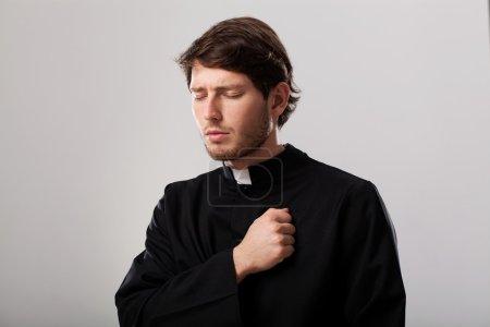 Photo pour Jeune prêtre chrétien regrette pour les péchés - image libre de droit