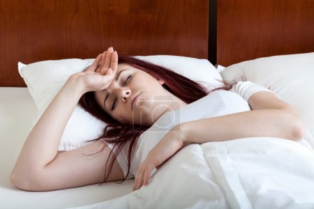 Woman with fever lying in bed