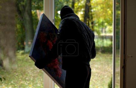 Photo pour Un voleur tenant une précieuse peinture volée - image libre de droit