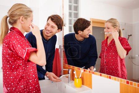 Photo pour Jeune couple pendant les activités quotidiennes dans la salle de bain - image libre de droit