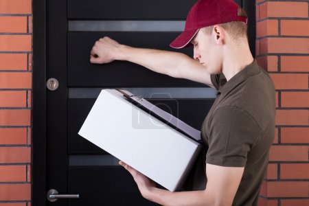 Photo for Courier knocking on a customer's door, horizontal - Royalty Free Image