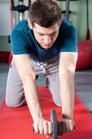 Man using abdominal roller