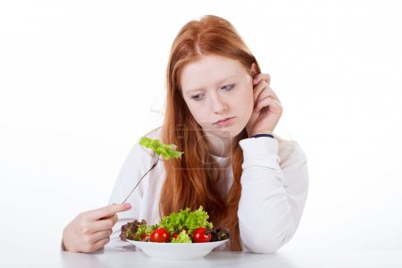 Photo for Teenage girl with no appetite on white isolated background - Royalty Free Image