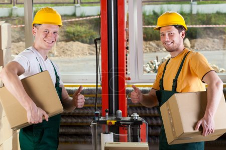 Factory workers showing thumbs up sign