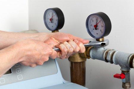 Man hands repairing pressure gauge and valve...