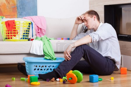 Photo pour Solitaire père fatigué, assis avec les jouets de l'enfant - image libre de droit