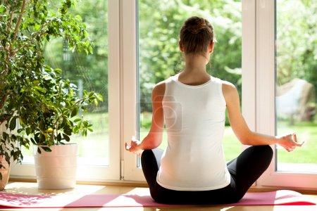 Photo pour Vue horizontale d'une femme faisant du yoga à la maison - image libre de droit