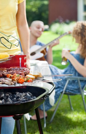 People grilling, playing guitar and singing