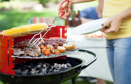 Photo for Young woman dishing up grilled meals during garden party - Royalty Free Image