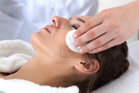Photo pour Gros plan de la femme pendant le nettoyage du visage dans le spa - image libre de droit