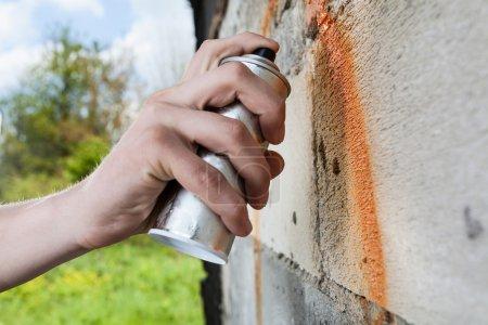 Photo pour Main tenant spray graffiti, le dessin sur le mur - image libre de droit