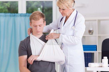 Photo pour Médecin portant une fronde pour revivre la douleur après la fracture - image libre de droit