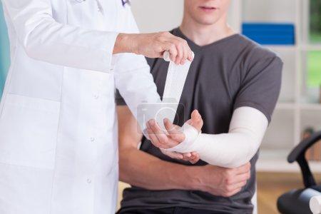 Doctor making cast of upper limb