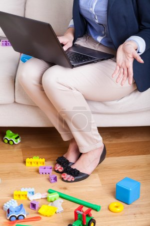 Photo for Mother working on laptop at home, vertical - Royalty Free Image