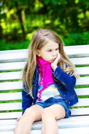 Photo for Sad blond little girl sitting on a bench in the park - Royalty Free Image