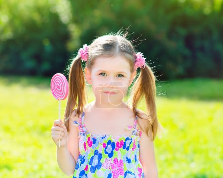 Adorable little girl with two blond ponytails holding white and pink lollipop in her hand, outdoor summer portrait