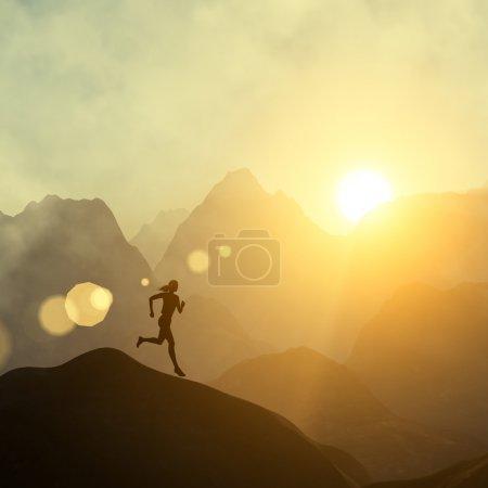 Foto de Silueta de una hermosa mujer corriendo colina abajo contra el cielo amarillo con nubes al atardecer - Imagen libre de derechos