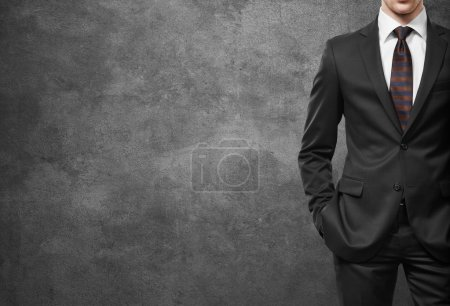 Photo for Man in suit on a dark concrete wall background - Royalty Free Image