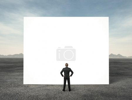Businessman looking at white empty billboard in the desert
