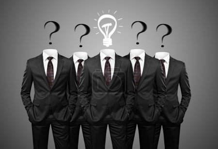 Businesssman with idea standind between other businessmen having questions instead of heads